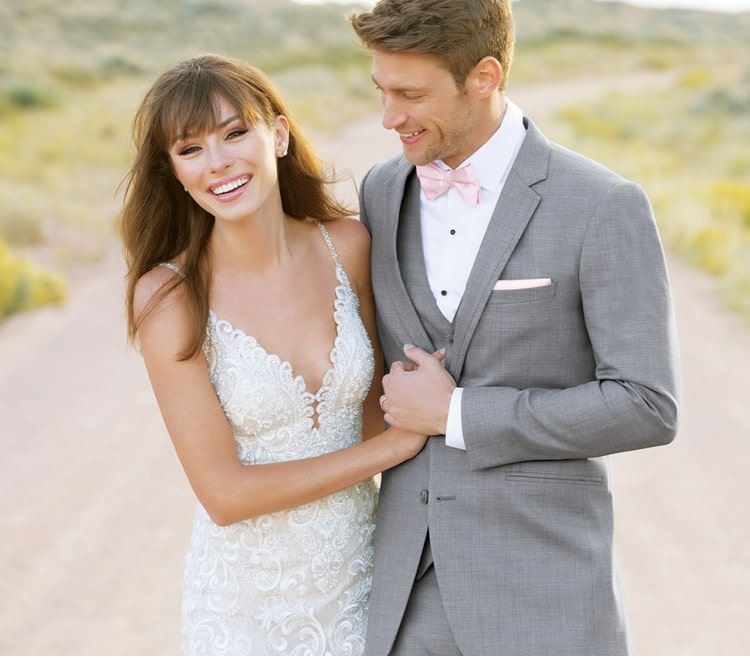 Bride and groom laughing while walking down path